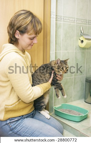 the Image of the girl showing to a cat its toilet