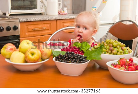 The image of the little girl eating fresh berries - stock photo