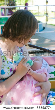 The image of the woman feeding the daughter from a children's small bottle - stock photo