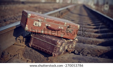 The image of two old vintage suitcases thrown on railway tracks. - stock photo