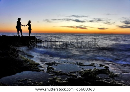 The image of two romantic people in love  standing at the sunset on the  rocky seashore