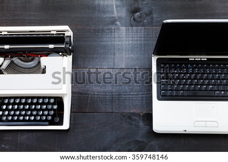 The image represents a retro typewriter and a laptop on a dark wood background conceptualizing that the time of technology is getting older the picture is taken from a top view - stock photo