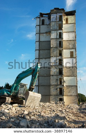 the image shows a digger demolishing a tower house