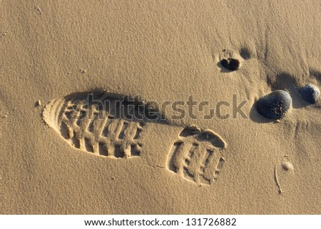 The imprint of the sole of a shoe, shows a footprint on the sand.