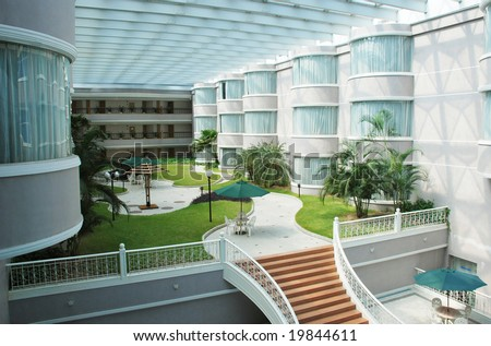The indoor garden in a luxury hotel patio  with glass and steel structured ceiling. - stock photo