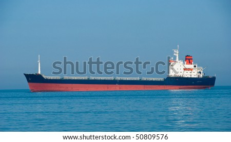 The industrial vessel - the dry-cargo ship goes to port - stock photo