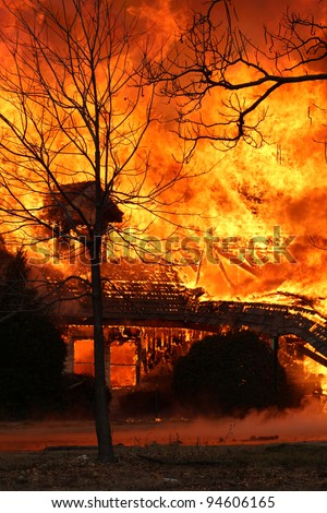 The inferno from the blaze of this out of control house fire is a warning to everyone to be aware of the thread of house fires which is a leading cause of accidental death. - stock photo