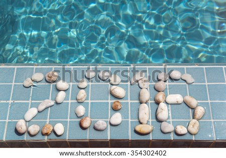 "The inscription "" 2016 "" is laid out by pebble on a pool side - stock photo"