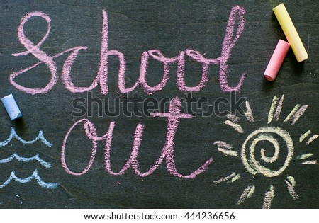 The inscription school out written on a blackboard