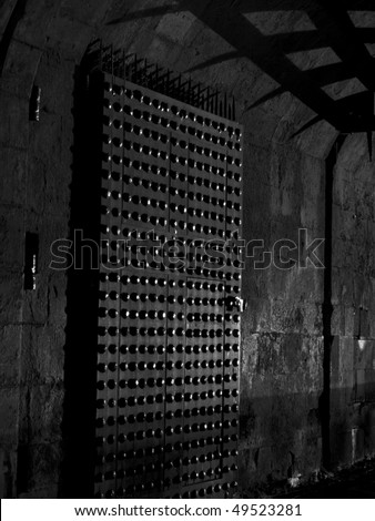 The inside castle gate to Edinburgh Castle at night shows a little bit of light reflecting off the metal studs in the door and shadows from the portcullis. In black and white. - stock photo