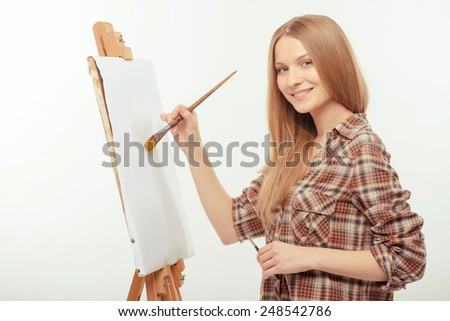 The inspiration is somewhere around. Young beautiful woman in a checked shirt painting with a brush on drawing easel with copy space while standing isolated against white background - stock photo