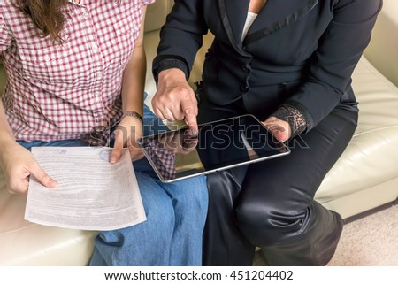 The insurance agent makes a deal, sign documents. The tablet in female hands. A woman touching the screen with her finger. - stock photo