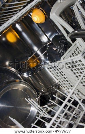 The interior of a dishwasher, with damp stainless steel, pots, pans and cutlery - stock photo