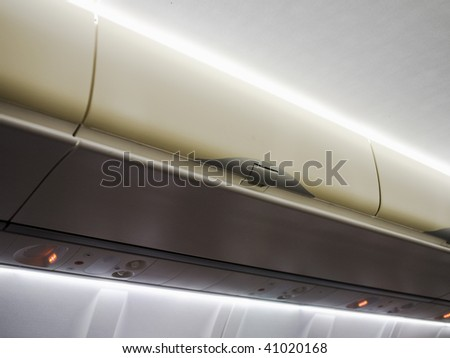 The interior of an airplane cabin with baggage - stock photo