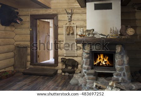The interior of the hunter's house with burning fireplace and stuffed boar head on the wall