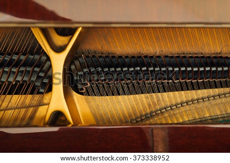 the internal mechanism of the strings in a grand piano - stock photo
