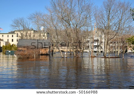 The Ipswich River engulfing a parking lot and surrounding local buildings
