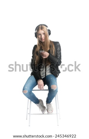 The isolated on white portrait of a teenager girl in wired headphones listening and enjoying music from personal portable device - stock photo