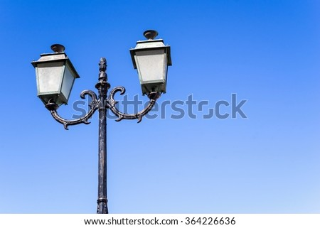 the isolated vintage lamp on an iron column against the blue sky