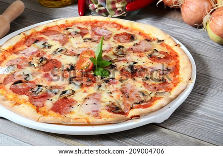 The Italian pizza with olives and salami - stock photo