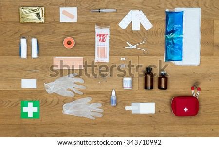 The items and objects in a first aid kit, neatly aligned on a wooden surface, including pliers, bandages, plaster, pills, heat or cold pack, isolation blanket, tape, rubber gloves,  and much more. - stock photo