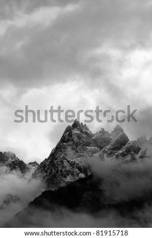 The jagged peaks of the Mont Blanc Massif appear through the clouds in Chamonix France. - stock photo