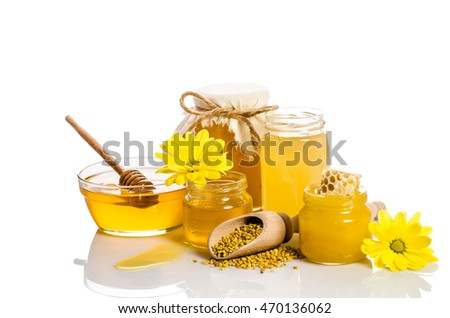 The jars of honey, one of them with honeycombs, glass bowl with honey and wooden scoop with pollen isolated on white
