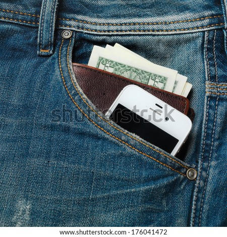 The jeans pocket with modern phone and a leather wallet full of money inside of it - stock photo