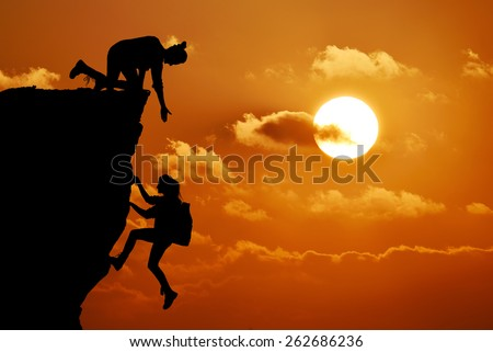 The joint work teamwork of two people man and girl travelers help each other on top of a mountain climbing team, a beautiful sunset landscape. - stock photo