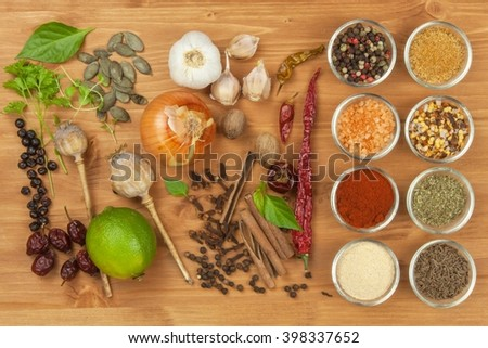 The joy of cooking, preparation of spices. Various kinds of spices on a wooden board. Food preparation. Spices on the kitchen table. - stock photo