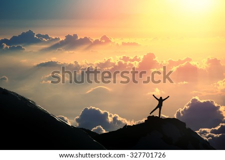 The joy of life. A person is standing on the top of the mountain above the clouds.  - stock photo
