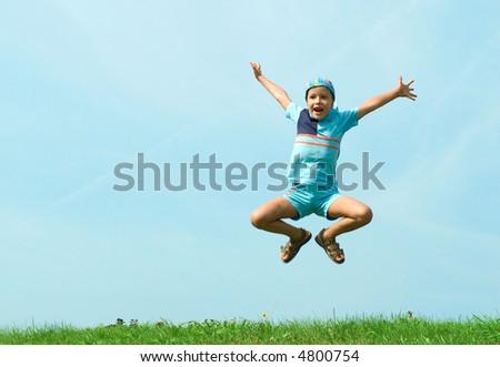 The joyful boy jumps on a background of blue sky - stock photo