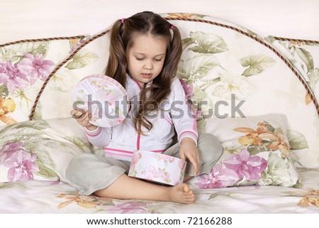The joyful girl sitting on a sofa opens a gift box - stock photo