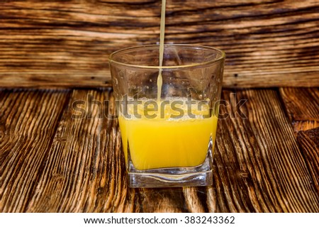 the juice is pouring into a glass - stock photo