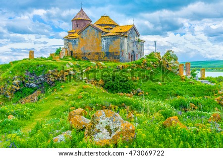 The juicy green hill with bright orange boulders, covered with lichen and moss, topped with the Church of Hayravank Monastery and its small cemetery, Armenia.