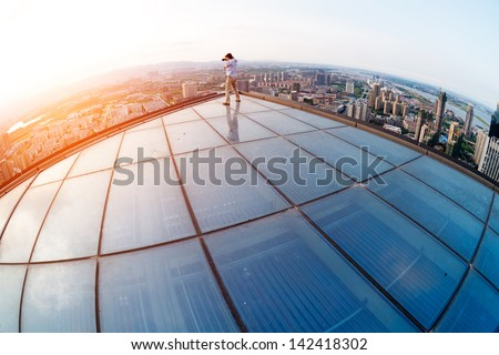 The keen photographer on a roof of the house - stock photo