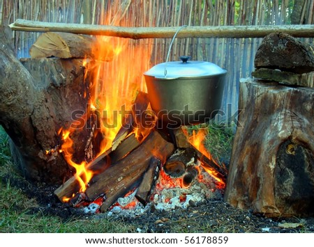 The kettle on a wooden crossbeam hangs over a fire