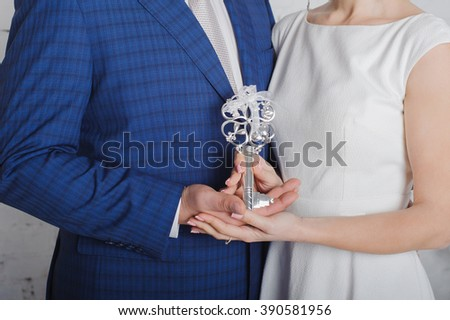 The key with heart in women and man hands as a symbol of love with heart . Big beautiful silver key with hearts. Real estate and relocation concept. Business success key concept vision  - stock photo