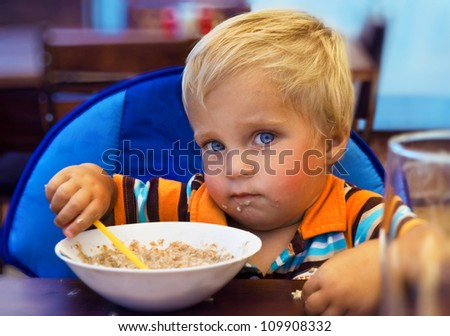 The kid eats porridge - stock photo