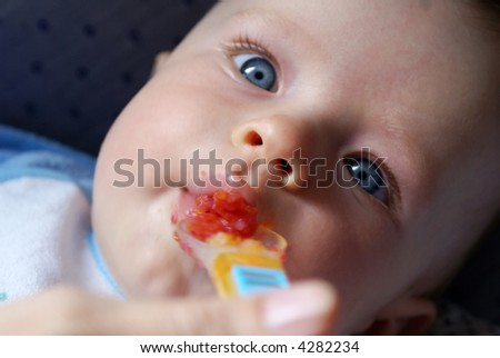 The kid feed from the spoon - stock photo