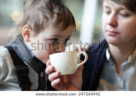 The kid has tea in the restaurant