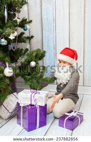 The kid is opening New Year presents at the Christmas tree - stock photo