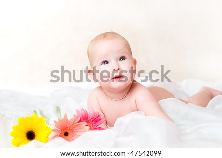 The kid lies on a white background with natural flowers. A high key  portrait