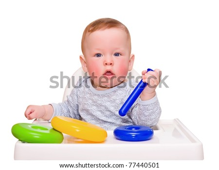 The kid, little table with a toy, on the white