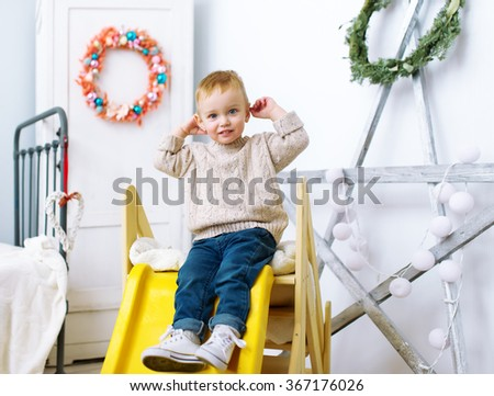 The kid plays in a nursery. In a nursery there is an attraction - a children's hill. - stock photo