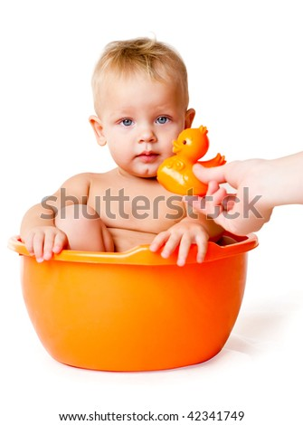 The kid sits in an orange basin after  bath, isolated on a white background - stock photo