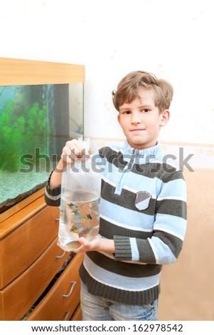 The kid stands near an aquarium - stock photo