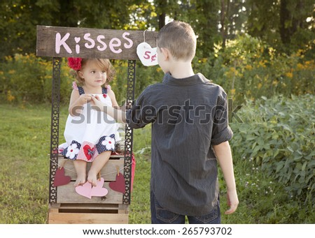The Kissing Booth.  Adorable toddler collecting money from a boy wanting to buy a kiss from her. - stock photo