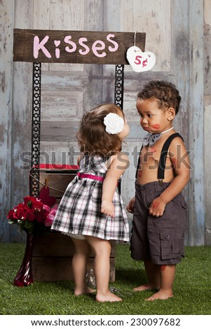 The Kissing booth.  Two adorable toddlers at a kissing booth. - stock photo