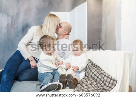 The kissing parents and and the playing children. Family house rest